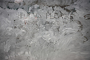 A message for help has been left on the inside of a vacant business in Cheapside (Street) in the City of London. Written back to front from inside, the writer has mis-spelled the word 'we're' . In the UK, vacant or redeveloped shops and businesses, are smeared with diluted white emulsion paint and water thereby obscuring the building's interior for security reasons.