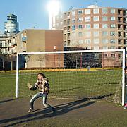 Nederland Rotterdam 7 maart 20110 20110307 Achterstandswijk Katendrecht. Meiden spelen een potje voetbal in de wijk op het grasveld. Deelgemeente Feijenoord,.Oud Zuid, omvat 4 probleemwijken die waarvan 1 Katendrecht.  spelenderwijs, sporten, sportende, sportief, sportieve, sporting, sportive, stadsdeel, stadse, stadswijk, stedelijke, straatbeeld, straatgezicht, straatvoetbal, street scenery, streetscene, vitaal, vitale, vitaliteit, voetballen, voetballer, voetballers, voetballertjes, voetbalpleintje, voetbalveld, voetbalveldje, vogelaarbuurt, vogelaarbuurten, vogelaarwijk, vogelaarwijken, voorziening, voorzieningen, vrije tijd, westerse allochtonen, westerse allochtoon, wijk, wijken, woonbuurt, woonbuurten, woonwijk, woonwijken, zichzelf vermaken, zonnig weer, zonnige dag Foto: David Rozing
