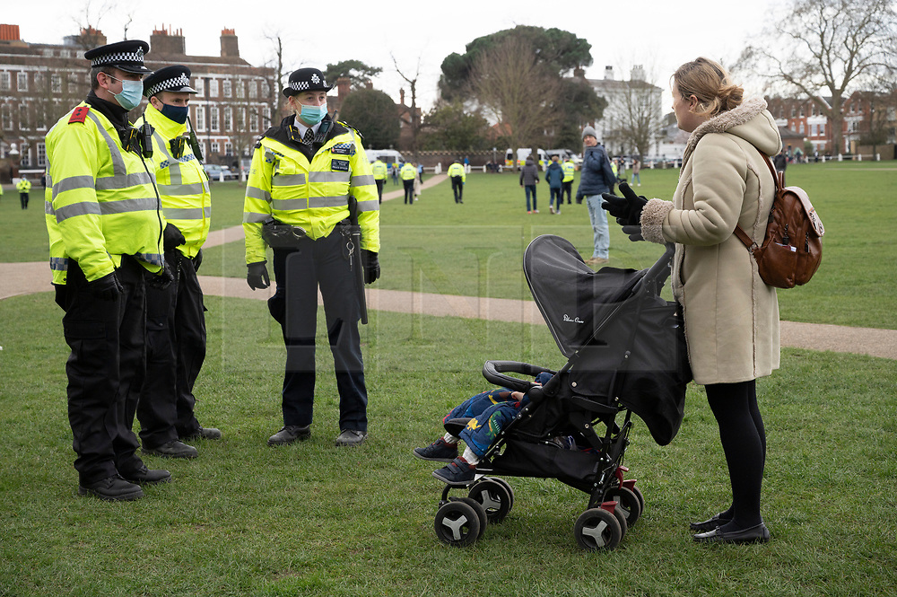 © Licensed to London News Pictures. 06/03/2021. London, UK. Police officers speak with a woman and child loving locally during an anti-vaccination and anti-lockdown demonstration organised by Jam For Freedom in Richmond. The group is using music to create positive effects and health against the current tier regulations and anti-vaccination for the Covid-19 disease. Photo credit: Ray Tang/LNP