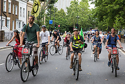 London, UK. 17 July, 2019. Climate activists from Extinction Rebellion take part in a Critical Mass bicycle ride from their camp on Waterloo Millennium Green to Hammersmith Town Hall on the third day of their 'Summer uprising'. The activists have three demands for Hammersmith and Fulham Council: to pass the proposed motion to declare a Climate Emergency; to keep Hammersmith bridge closed to vehicles; and to commit to safer cycling routes.