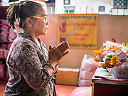 """10 AUGUST 2014 - BANGKOK, THAILAND: A woman prays on the first day of Ghost Month at the Poh Teck Tung Shrine in Bangkok. The seventh month of the Chinese Lunar calendar is called """"Ghost Month"""" during which ghosts and spirits, including those of the deceased ancestors, come out from the lower realm. It is common for Chinese people to make merit during the month by burning """"hell money"""" and presenting food to the ghosts.    PHOTO BY JACK KURTZ"""