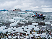 People from the M/S Explorer dodge icebergs to arrive via a Zodiac boat wet landing on Cuverville Island, Antarctica. The rocky Cuverville Island is in Errera Channel off the west coast of Graham Land, the north portion of the Antarctic Peninsula, Antarctica. In summer, Cuverville is often home to a large rookery of Gentoo Penguins. The island was discovered by the Belgian Antarctic Expedition (1897-1899) under Adrien de Gerlache, who named it for J.M.A. Cavelier de Cuverville (1834-1912), a vice admiral of the French Navy. Cuverville Island or Île de Cavelier de Cuverville is located at 64 degrees 41 minutes South Latitude and 62 degrees 38 minutes West Longitude.