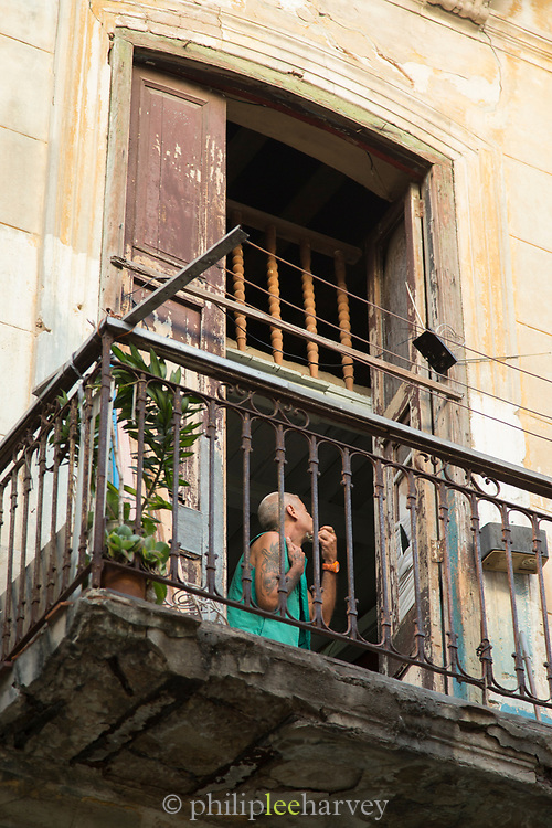 Low angle view of balcony and man in his home shaving, Havana, Cuba