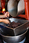 Fresh chocolate paste come out of a grinding and mixing machine in Oaxaca, Mexico.