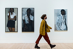 "© Licensed to London News Pictures. 02/12/2020. LONDON, UK. A staff member passes (L to R) ""A Fever of Lilies"", 2016, (diptych) and ""For The Sake of Angels"", 2018. Preview of ""Lynette Yiadom-Boakye: Fly In League With The Night"" the first major UK survey exhibition by British artist Lynette Yiadom-Boakye.  Over 70 of her works spanning two decades are on display at Tate Britain.  It is the first new exhibition at Tate since the galleries were re-opened after coronavirus lockdown restrictions were slightly eased by the UK government.  Photo credit: Stephen Chung/LNP"