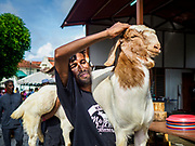 "22 AUGUST 2018 - GEORGE TOWN, PENANG, MALAYSIA:  Workers carry goats into Kapitan Keling Mosque for sacrifice during Eid al-Adha services at the mosque in George Town. It is the oldest mosque in George Town. Eid al-Adha, ""Feast of the Sacrifice"" is the second of two Islamic holidays celebrated worldwide each year. It honors the willingness of Ibrahim (Abraham) to sacrifice his son as an act of obedience to God's command.   PHOTO BY JACK KURTZ"