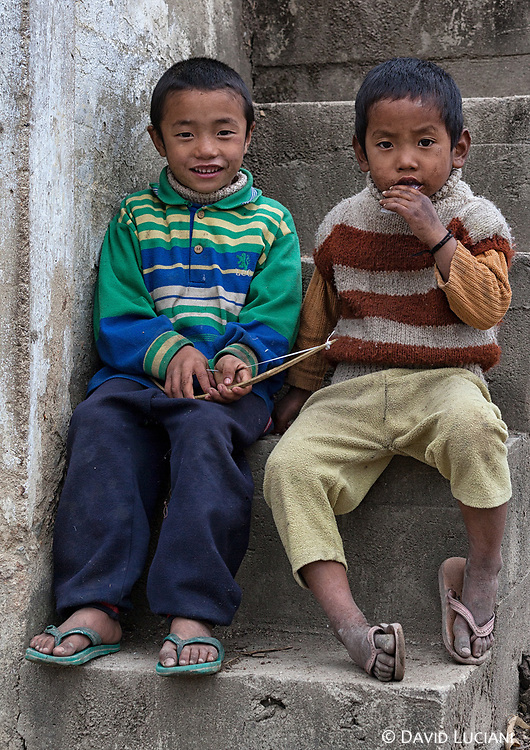 Two boys sitting on the stairs of their house in Hari village.