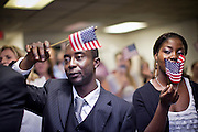 "June 21, 2010 - PHOENIX, AZ:  REGINALD NEWLOVE (left) from Sierra Leone, and TABITHA MAMATTAH, from Liberia, sing ""God Bless the USA"" during a naturalization ceremony for former refugees at the International Rescue Committee offices in Phoenix, AZ, Monday, June 21. World Refugee Day was Sunday, June 20; the IRC and US Citizenship and Immigration Services offices  marked the day by holding a naturalization ceremony for 10 people who came to the US as refugees.  Photo by Jack Kurtz"