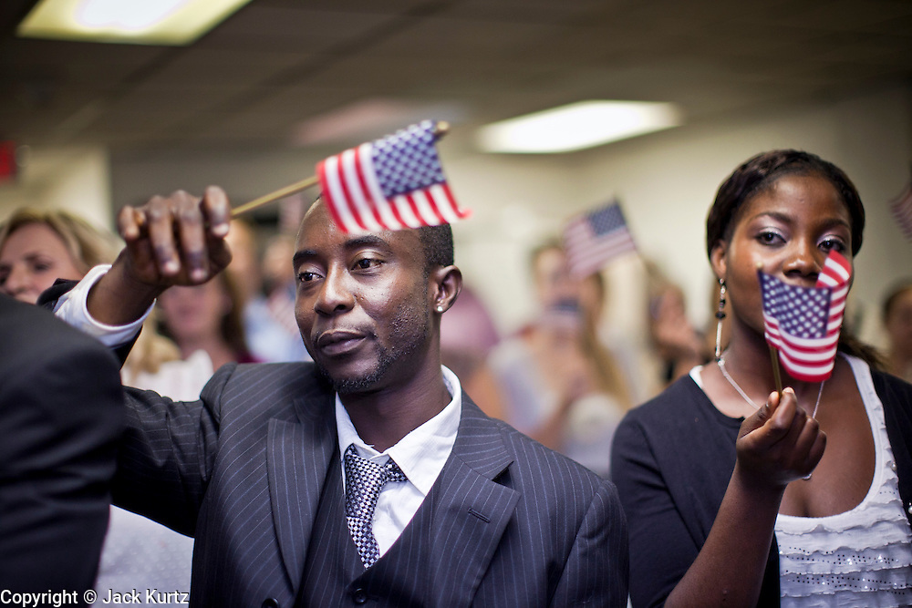 """June 21, 2010 - PHOENIX, AZ:  REGINALD NEWLOVE (left) from Sierra Leone, and TABITHA MAMATTAH, from Liberia, sing """"God Bless the USA"""" during a naturalization ceremony for former refugees at the International Rescue Committee offices in Phoenix, AZ, Monday, June 21. World Refugee Day was Sunday, June 20; the IRC and US Citizenship and Immigration Services offices  marked the day by holding a naturalization ceremony for 10 people who came to the US as refugees.  Photo by Jack Kurtz"""