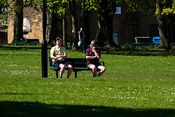 Hillsborough Park Sheffield two men sit on either end of a bench during week 4 of the UK Covid-19 Emergency Measures to combat the Coronavirus pandemic<br /> <br /> 15 April 2020<br /> <br /> www.pauldaviddrabble.co.uk<br /> All Images Copyright Paul David Drabble - <br /> All rights Reserved - <br /> Moral Rights Asserted -