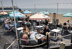 © Licensed to London News Pictures. 24/06/2021. Brighton, UK. Visitors to Brighton enjoy a meal outdoors on the beach during warm and sunny weather. After recent rain, a period of high temperatures and sunshine is forecast in the south. Photo credit: Peter Macdiarmid/LNP