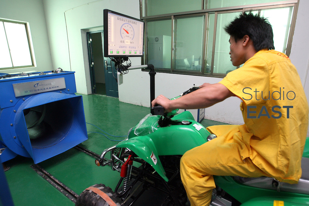 A testing worker, recognizable for his yellow outfit, tests the speed and wind resistance of an ATV in Easy vehicle laboratory, in Yong Kang, Zhejiang province, China, on September 17, 2007. Photographer: Lucas Schifres/Pictobank