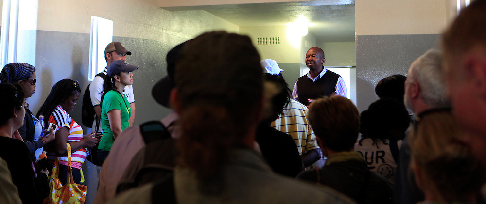 Tourists listen to a former prisoner on Robben Island (who is now a guide) in one of the detention buildings of Robben Island. The island where Nelson Mandella was held prisoner near Cape Town, South Africa.  Photo by Dennis Brack...