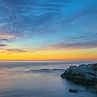 Sunrise panorama photography of the iconic Portland Head Light at Fort Williams Park which is a classic New England landmark located on Cape Elizabeth in Maine. The lighthouse towers over the swirling Atlantic Ocean and seacoast, marking the entrance to Casco Bay and Portland. Upon arrival the gates to the park were already open leaving me enough time to scout for an appropriate composition that allows to incorporate the anticipated magical morning show in the sky and some of the dramatic seascape of coastal Maine.<br />