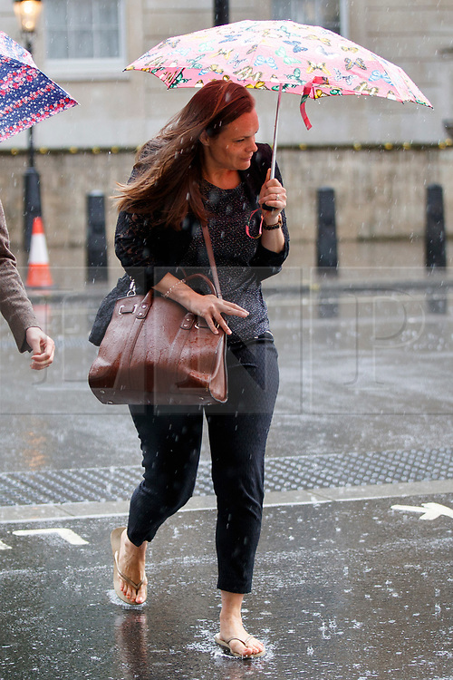 © Licensed to London News Pictures. 27/06/2017. London, UK. A woman with summer shoes takes shelter from the rain on Whitehall in London on Tuesday, 27 June 2017. Photo credit: Tolga Akmen/LNP