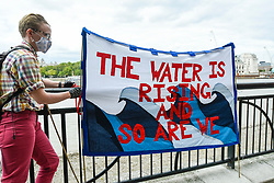 "© Licensed to London News Pictures. 06/09/2020. LONDON, UK.  An activist from Extinction Rebellion (XR) with a banner takes part in a ""Flood Alert"" protest on the shore of the River Thames near Gabriel's Wharf on the South Bank to highlight the effects of climate change on rising sea levels.  Photo credit: Stephen Chung/LNP"