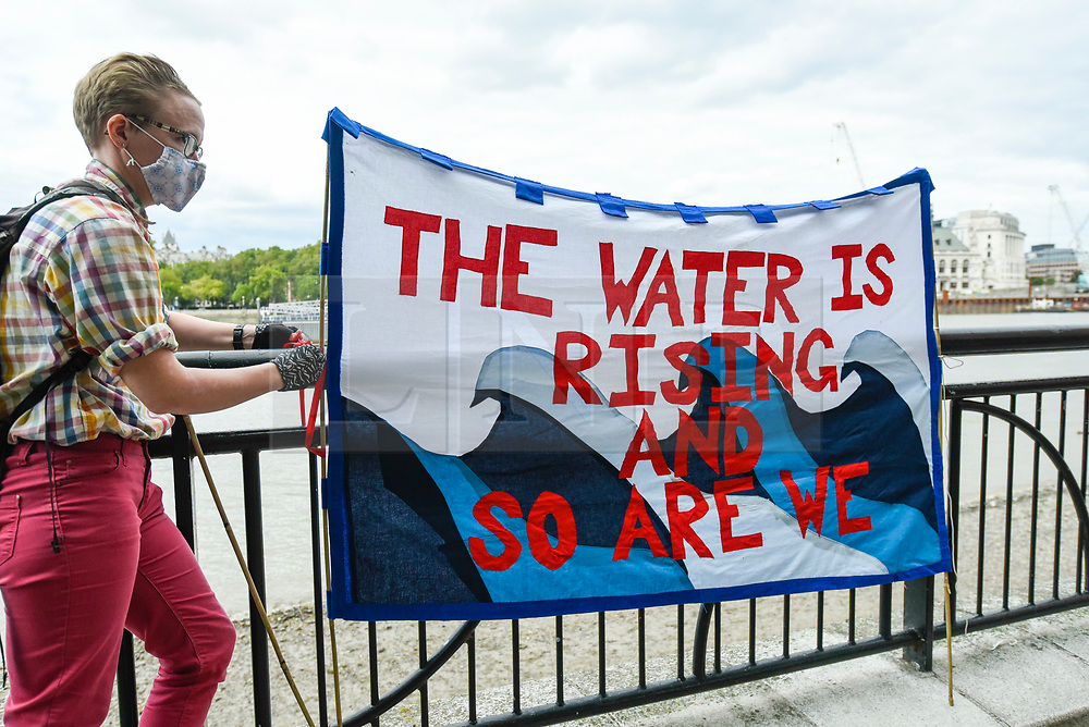"""© Licensed to London News Pictures. 06/09/2020. LONDON, UK.  An activist from Extinction Rebellion (XR) with a banner takes part in a """"Flood Alert"""" protest on the shore of the River Thames near Gabriel's Wharf on the South Bank to highlight the effects of climate change on rising sea levels.  Photo credit: Stephen Chung/LNP"""