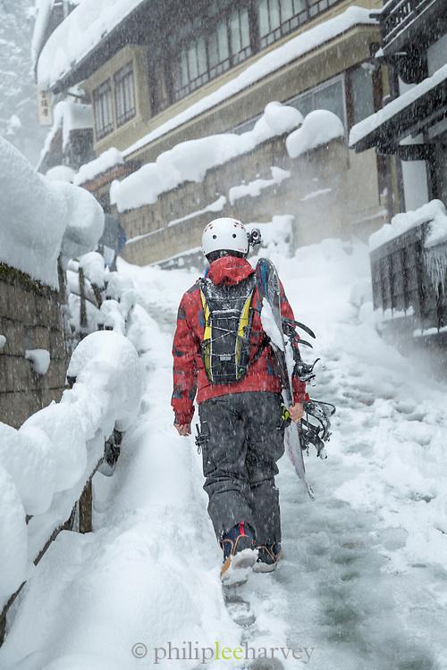 Rear view of man walking in snow, Nagano, Japan