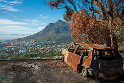 This is overlooking Cape Town from the Lion's head parking lot, during lockdown in South Africa, on April 10, 2020. The burned out car is a relic from recent fires. PHOTO: EVA-LOTTA JANSSON<br /> [This is one is a series of landscapes shot in the Western Cape, South Africa, during the national lockdown in response to the Coronavirus.]