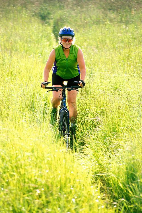 A mature woman riding a mt bike through a grassy field.