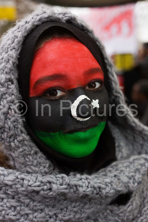 A detail of a young exiled Libyan woman who has painted her face in the colours of the pre-revolutionary flag that Libyans have adopted as their new flag after Gaddafi's downfall, During the protests opposite her London embassy, the woman shows us the flag of the independent kingdom: Red, black, and green with a crescent and star in the centre. After the Libyan revolution of 1969, the flag was changed to the Arab Liberation Flag of horizontal red, white, and black bands. In 1971 Libya joined the Federation of Arab Republics with Egypt and Syria, which used a similar flag with a hawk emblem in the center and the name of the country beneath it. When Libya left the Federation in 1977, the new plain green flag was adopted. But during the 2011 uprising, the old flag was once again adopted.