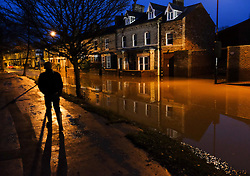 © Licensed to London News Pictures. 29/12/15<br /> York, UK. <br /> <br /> A man walks along the pavement as flood water begins to subside on Huntington Road in York. Further rainfall is expected over coming days as Storm Frank approaches the east coast of the country.<br /> <br /> Photo credit : Ian Forsyth/LNP