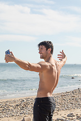shirtless man enjoying a taking a selfie on a beach