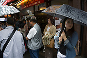 London, UK. Sunday 23rd August 2015. Heavy summer rain showers in the West End. People brave the wet weather armed with umbrellas and waterproof clothing. Tourists on Gerrard Street in Chinatown.