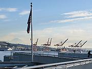 Cranes of the Port of Seattle. Mount Rainier. US flag. Downtown Seattle, Washington, USA.