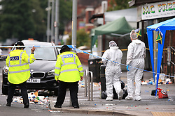 Police officers and forensics at the scene in Claremont Road, Moss Side, Manchester, where several people have been injured after a shooting.