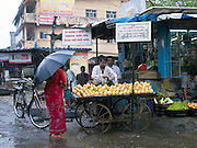 Shopkeeper selling fruit in a market during the monsoon rains, Goa, India