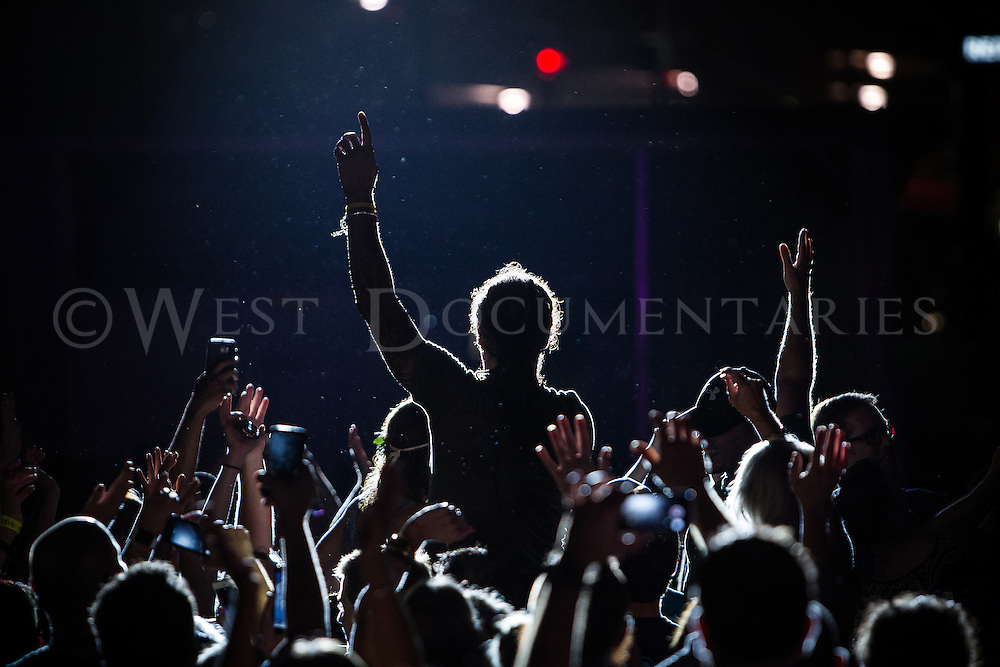 Michael Franti joins the crowd in celebration during the rain at Red Hat Amphitheater during one of the bands songs on June 27, 2015 at the Band Together benefit Concert.