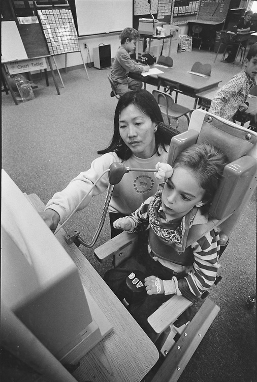 ©1990 Kindergarden teacher working with cerebral palsy students on Apple Computer.