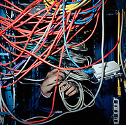 An IT support worker wrestles with a spaghetti of cables serving the computer systems  at a trading company.From the series Desk Job, a project which explores globalisation through office life around the World.