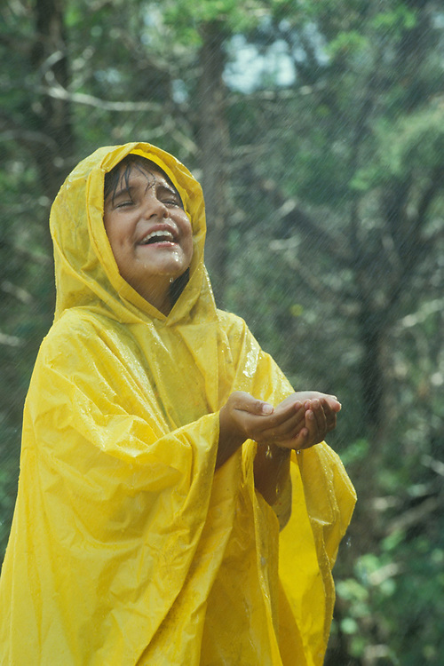 Young Hispanic girl, 4th grader, standing outside in the rain while wearing yellow rain jacket/pullover.  Model Release.<br /> ©Bob Daemmrich