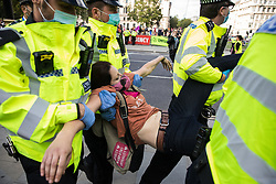 Metropolitan Police officers arrest a climate activist from Extinction Rebellion who had occupied a road around Parliament Square during a Back The Bill rally on 1st September 2020 in London, United Kingdom. Extinction Rebellion activists are attending a series of September Rebellion protests around the UK to call on politicians to back the Climate and Ecological Emergency Bill (CEE Bill) which requires, among other measures, a serious plan to deal with the UK's share of emissions and to halt critical rises in global temperatures and for ordinary people to be involved in future environmental planning by means of a Citizens' Assembly.