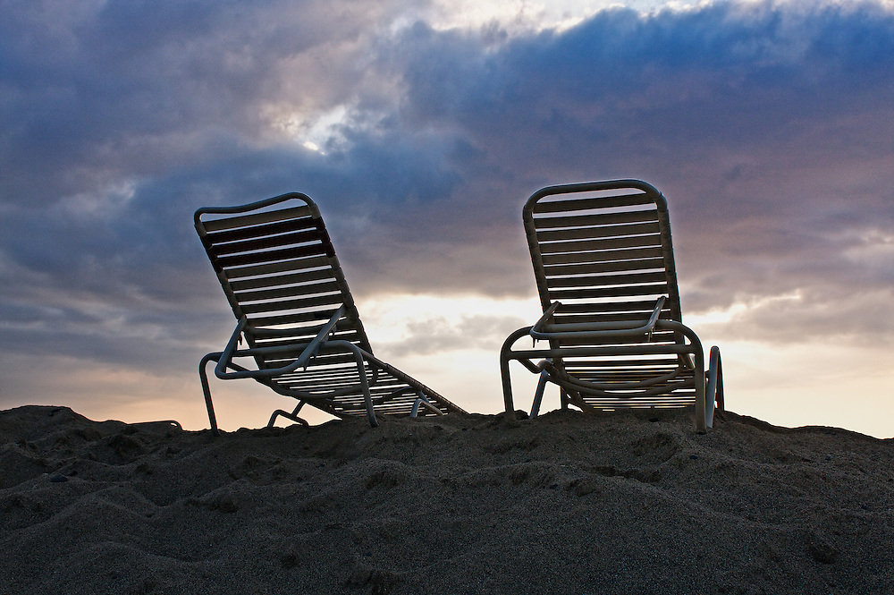 Lounge chairs on the beach bask in the evening sun.