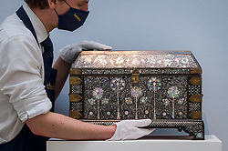 "© Licensed to London News Pictures. 29/03/2021. LONDON, UK. A staff member presents ""An exceptional mother-of-pearl casket"" (est. £250,000-350,000). Preview of the upcoming Arts of the Islamic World & India sale where historic objects, paintings and manuscripts from the last 1,000 years are to be auctioned on 31 March at Sotheby's New Bond Street galleries.  Photo credit: Stephen Chung/LNP"
