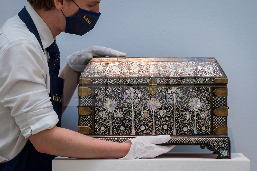 """© Licensed to London News Pictures. 29/03/2021. LONDON, UK. A staff member presents """"An exceptional mother-of-pearl casket"""" (est. £250,000-350,000). Preview of the upcoming Arts of the Islamic World & India sale where historic objects, paintings and manuscripts from the last 1,000 years are to be auctioned on 31 March at Sotheby's New Bond Street galleries.  Photo credit: Stephen Chung/LNP"""