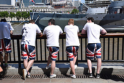Young men wearing Union Jack shorts in front of HMS Belfast, London Summer 2017 UK