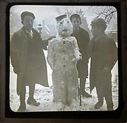 Magic lantern slide three boys making a snowman in a garden, England, UK c 1900-1910