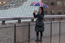 © Licensed to London News Pictures. 02/01/2018. London, UK. Pedestrians shelter under umbrellas on London Bridge amid torrential rainfall. Storm Eleanor is expected to bring high winds and heavy rain to much of the United Kingdom, with flooding expected. Photo credit: Rob Pinney/LNP