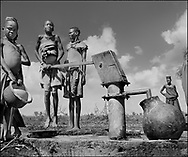 Karamajong Children at a LWF water well filling containers. Many of the children had walked several miles to fetch water. Karamajong of Karamoja, Uganda 1980