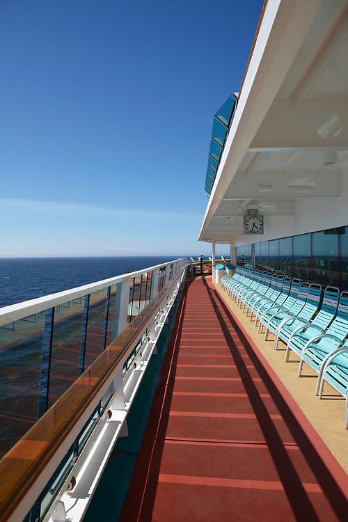 Wide angle view of an empty cruise ship deck on the open ocean with blue sky and no clouds
