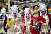 Pride in London, formally known as Pride London, is an annual LGBT pride festival and parade held each summer in London, United Kingdom. A group of bearded men march in elaborate white wigs and  theatrical costumes, and hold feather fans.