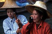 Vendor chats on mobile phone, at the floating market, Damnoensaduak, Thailand