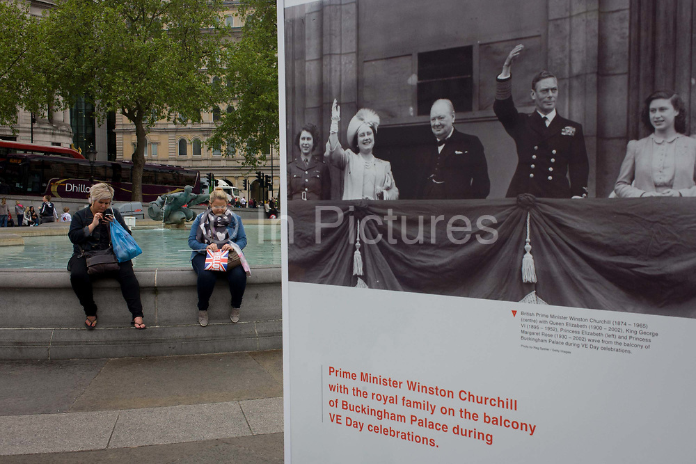 Visitors interact with an outdoor photography exhibit where on this day 70 years ago, Victory in Europe (VE) Day was celebrated by the royal family and Winston Churchill and ecstatic crowds rejoicing the end of WW2, on the streets of London and here, in Trafalgar Square. In a scene of changing times, we see the modern Briton as an obese population, obssessed with the trivial and meaningless while their forbears endured wartime hardship and years of austerity that followed the 1945 end of hostilities.