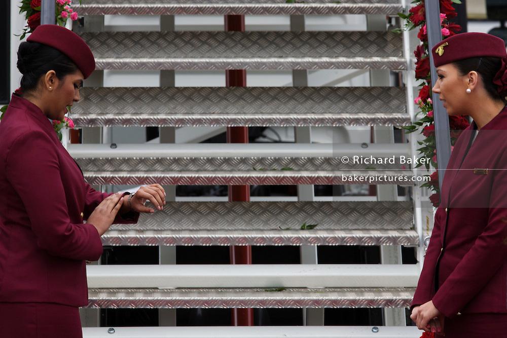 Cabin crew hostess checks her watch at the bottom of steps a Qatar Airways Boeing 787 at the Farnborough Air Show, UK.