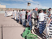 """04 FEBRUARY 2009 -- Chains and shackles are removed from undocumented immigrant prisoners at the gates to tent city. Maricopa County Sheriff Joe Arpaio marched about 200 undocumented immigrants in the Durango Jail to """"Tent City"""" where he will house the prisoners until or if they are deported. PHOTO BY JACK KURTZ"""
