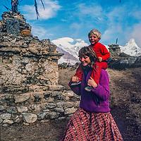 Meredith Wiltsie & 3-year old son Ben trek past a Tibetan Buddhist chorten while trekking  in the Khumbu Region of Nepal, with Mount s Everest, Lhotse and Ama Dablam  in background.